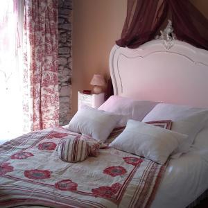 A bed or beds in a room at Chambres d'hôtes - Au Domaine des Camélias