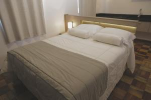 A bed or beds in a room at Rodeio Hotel