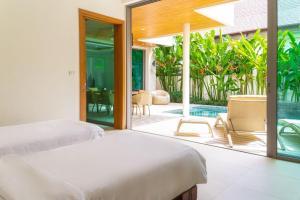 Кровать или кровати в номере Rawai Ka 4-Bedroom Villa