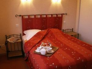 A bed or beds in a room at Logis L'Auberge du Quercy Blanc