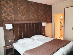 A bed or beds in a room at Aadam Hotel Wilhelmina