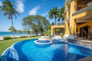 The swimming pool at or near 4-bedroom beachfront mansion is a few paces from the waves