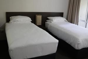A bed or beds in a room at Reef Resort Villas Port Douglas