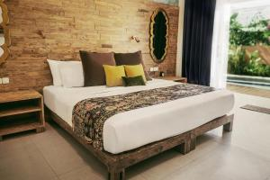A bed or beds in a room at Pesona Beach Resort & Spa