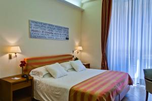 A bed or beds in a room at Crosti Hotel