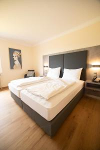 A bed or beds in a room at Das Reinisch Just Rooms