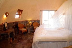 A bed or beds in a room at Rostock Ritz Desert Lodge