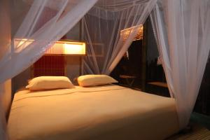 A bed or beds in a room at Ecolodge Bukit Lawang