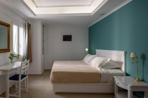 A bed or beds in a room at Villa Renos Hotel