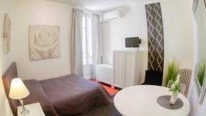 A television and/or entertainment centre at SeaYouSoon Inn Cannes - Studios