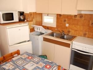 A kitchen or kitchenette at Rental Apartment Les Zodiaques 2