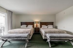 A bed or beds in a room at Beach Cove Waterfront Inn