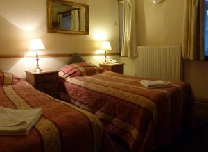 A bed or beds in a room at Riverside Hotel
