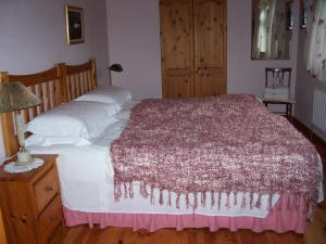 A bed or beds in a room at An Caladh Gearr Thatch Cottage