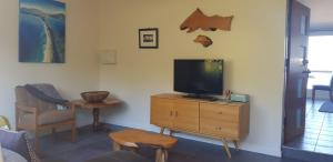 A television and/or entertainment center at Discover Bruny Island Holiday Accommodation