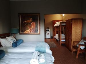 A bed or beds in a room at Raintree Guest House