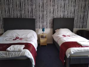 A bed or beds in a room at Aberdeen Arms Hotel Tarland