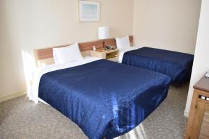 A bed or beds in a room at Asakusa Central Hotel