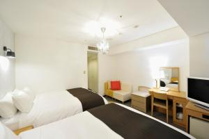 A bed or beds in a room at Court Hotel Shin-Yokohama