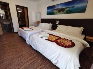 A bed or beds in a room at The Barat Tioman Beach Resort