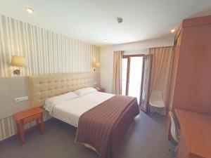 A bed or beds in a room at Hotel Rambla Emerita