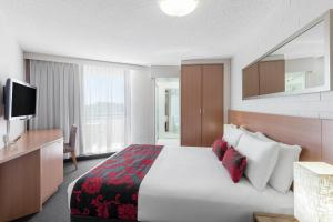 A bed or beds in a room at Ramada By Wyndham Marcoola Beach