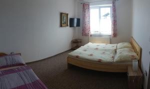 A bed or beds in a room at Penzion Panter