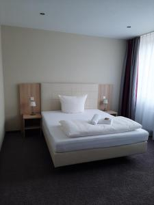 A bed or beds in a room at Hotel Siebenschläfer am Wasserturm