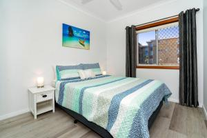 A bed or beds in a room at Beachcomer, Unit 2 - The Entrance, NSW