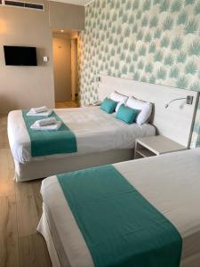 A bed or beds in a room at Harmony Bay Hotel