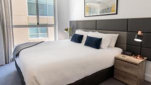 A bed or beds in a room at Oaks Glenelg Plaza Pier Suites