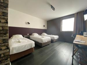 A bed or beds in a room at Hotel O Ieper