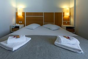 A bed or beds in a room at Fedriades Delphi Hotel