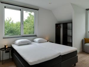 A bed or beds in a room at Luxury 6 person home on the island of Texel with sauna and sun shower