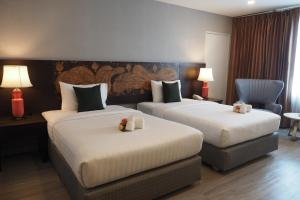 A bed or beds in a room at Empress Pattaya Hotel