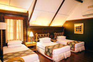 A bed or beds in a room at Mutiara Taman Negara Resort
