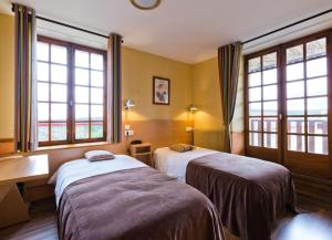A bed or beds in a room at Hôtel La Clairière
