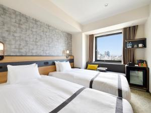 A bed or beds in a room at Hotel Elcient Osaka