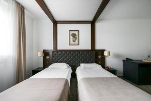 A bed or beds in a room at Amberton Cozy Hotel Kaunas