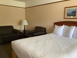A bed or beds in a room at Luxury Inn & Suites