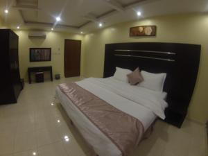 سرير أو أسرّة في غرفة في فخامة الارجوانة للأجنحة الفندقية