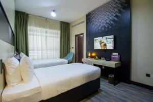 A bed or beds in a room at TIME Express Hotel Al Khan