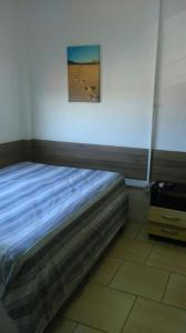 A bed or beds in a room at Hotel Passarela