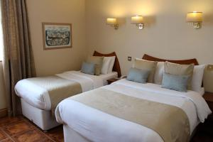 A bed or beds in a room at Uppercross House Hotel