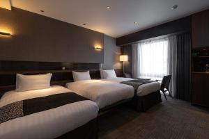 A bed or beds in a room at Hotel Trad Hakata