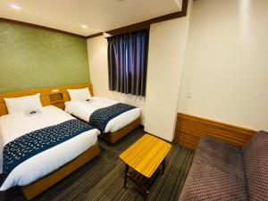 A bed or beds in a room at Ueno Touganeya Hotel