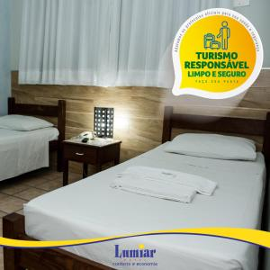 A bed or beds in a room at Hotel Lumiar
