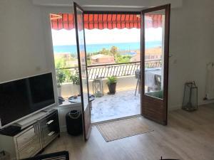 A television and/or entertainment centre at Appartement 2 chambres, vue mer panoramique, grande terrasse, proche de la plage