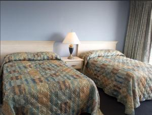 A bed or beds in a room at Acropolis Oceanfront Resort
