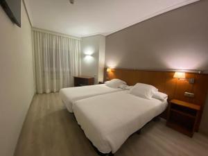 A bed or beds in a room at Hotel Ciudad de Compostela